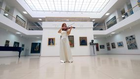 One musician in white dress plays violin in a museum. 4K stock video footage