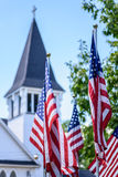 One nation under God - US flags in front of white church steeple. American flags waving in breeze with soft focus church steeple in background Stock Photos