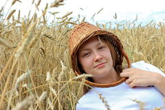 At one with nature. Young lady with basket on her head relaxing in a field Royalty Free Stock Photography