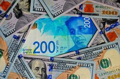 One new banknote of 200 Israeli shekels and a lot of bills of 100$. Top view, background. stock photography