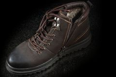 One new brown suede winter boot on a dark granite, top view.  Royalty Free Stock Photography