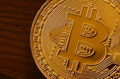 One new golden physical bitcoin is lies on dark wooden backgound, close up. High resolution photo. Cryptocurrency mining concep. T Stock Images