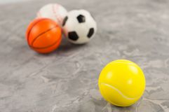 One new rubber soft tennis ball on background of three different sports balls royalty free stock photography