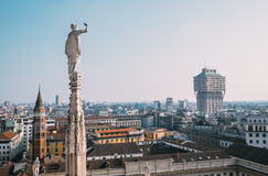 One of numerous ststues Duomo di Milano looks on modern city Stock Image
