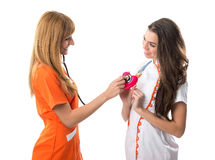 One nurse listens to the other nurse's heart Royalty Free Stock Images