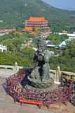 One of The Offering of the Six Devas Buddhistic statues with Po Lin Monastery. In background. The statues are praising and making offerings to the Tian Tan stock image