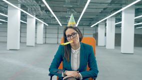 One office worker in a birthday cap blows a whistle, sitting in a chair. stock footage