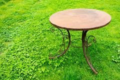 One old iron table is located on a lawn Royalty Free Stock Photography