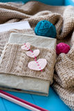 One old notebook in knitted cover with felt hearts Stock Photo