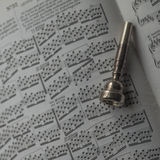 One old Silver Trumpet mouthpiece on sheet music book. A silver trumpet mouthpiece on sheet music book Stock Photo