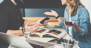 One on one meeting.Teamwork,young designers are sitting at table in office and pick up finishing materials in catalog. Royalty Free Stock Images