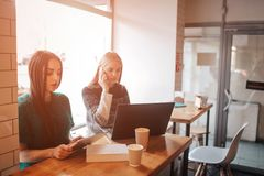 One-on-one meeting.Two young business women sitting at table in cafe. Girl shows colleague information on laptop screen. Girl using smartphone, blogging Royalty Free Stock Photo