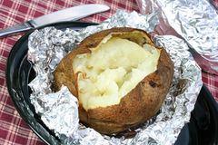 One open baked potato on aluminum foil, unwrapped. Royalty Free Stock Photos