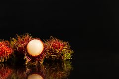 One open and a few closed rambutans on a mirror with a black background royalty free stock photo