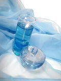 One opened bottle of perfume on a blue background with candle Royalty Free Stock Photo
