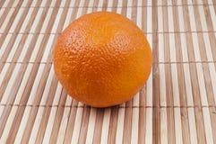 One orange. On bamboo background Stock Image