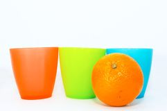 One orange fruit and cups. One oranges with cups on white stock images