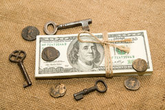 One pack of dollars, coins and keys on an old cloth Stock Photo