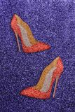 Women red shoes with glitter on a purple glittery background. One pair of beautiful red sexy high-end shoes with high heels on a violet purple background Royalty Free Stock Photos