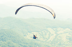 One paraglider on summer day over the green hills Stock Image