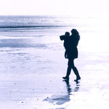 One parent family. Square image of one parent family alone a empty seafront, lots of room in the background  for text a poem or a message . Blue filter added Royalty Free Stock Images