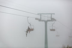 One passenger with bike on chair lift in the fog. Stock Image