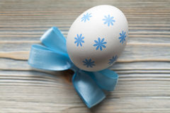 One patterned Easter egg and blue bow stock image