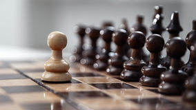 One pawn staying against full set of chess pieces. Stock Photography