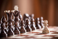 One pawn staying against full set of chess pieces. Royalty Free Stock Images