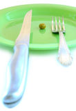 One pea on green plate. One pea on green plastic plate, fork and knife royalty free stock photography