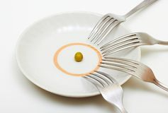 One pea and many forks stock photo