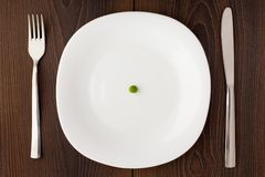 One pea on a white plate Stock Photo