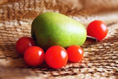 One pear and tomatos. One pear and tomato on paper layer Stock Photo