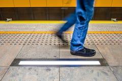 one pedestrian in blue jeans walks along tactile paving for visu stock image
