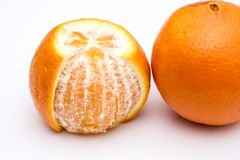 The one peeled orange and one unpeeled on the white background royalty free stock photos