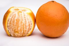 The one peeled orange and one unpeeled on the white background royalty free stock image