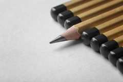 One pencil standing out from others. On color background. Difference and uniqueness concept royalty free stock photo