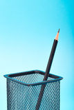 One pencil in a wire mesh. Pencil holder, Blue background royalty free stock photo