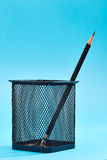 One pencil in a wire mesh pencil. Holder, Blue background royalty free stock image
