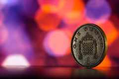 One penny on a background of orange bokeh. One penny close up on a background of blue bokeh Royalty Free Stock Image