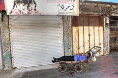 One persian male loader sleeps in a hand trolley. Royalty Free Stock Image