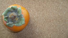 One Persimmon on a Cork background Royalty Free Stock Photos