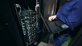 One person checks data center equipment, working with a laptop. stock video footage