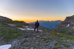 One person looking at colorful sunrise high up in the Alps. Wide angle view from above with glowing mountain peaks in the backgrou. Nd. Summer adventure and Royalty Free Stock Images