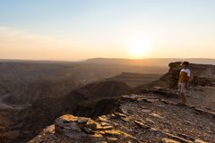 One person looking at the Fish River Canyon, scenic travel destination in Southern Namibia. Expansive view at sunset. Wanderlust t. Raveling people Royalty Free Stock Photography