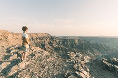 One person looking at the Fish River Canyon, scenic travel destination in Southern Namibia. Expansive view at sunset. Wanderlust t. Raveling people Stock Photography