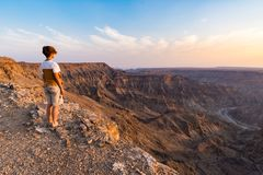One person looking at the Fish River Canyon, scenic travel destination in Southern Namibia. Expansive view at sunset. Wanderlust t. Raveling people Royalty Free Stock Images