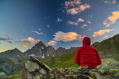 One person looking at the majestic view of glowing mountain peaks at sunset high up on the Alps. Rear view, toned and filtered ima Stock Image
