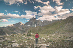 One person looking at the majestic view of glowing mountain peaks at sunset high up on the Alps. Rear wide angle view, toned and f Stock Photos