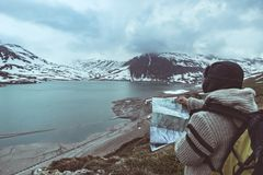 One person looking at trekking map, dramatic sky at dusk, lake and snowy mountains, nordic cold feeling.  Stock Images